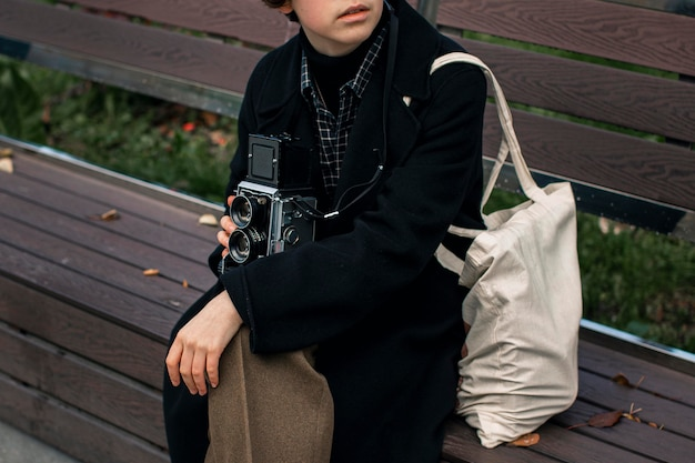 Non binary person holding a retro camera while sitting on a bench