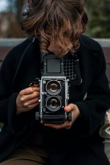 Non binary person holding a retro camera
