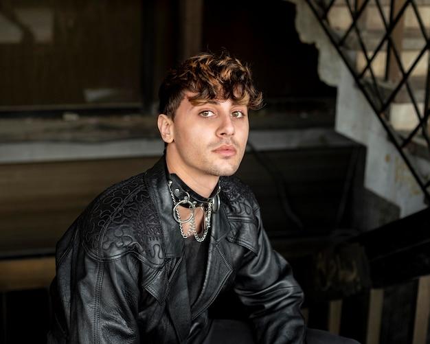 Небинарный человек в кожаной куртке сидит на лестнице