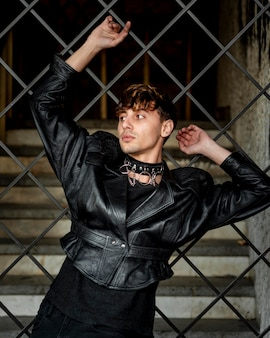 Non binary person in leather jacket posing on a metallic fence