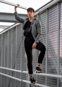 Non binary person posing on a metallic fence