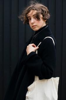 Persona non binaria in posa con borsa bianca