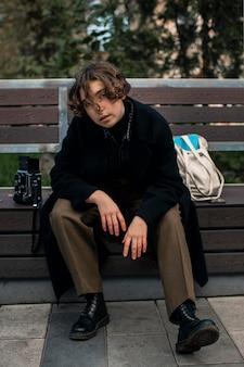 Небинарный человек сидит и позирует на скамейке