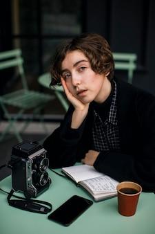 Небинарный человек, сидящий за столом в ретро-одежде