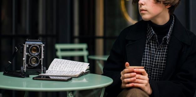 Небинарный человек, сидящий за столом на улице