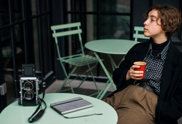 Небинарный человек в ретро-одежде и пьёт кофе