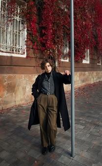 Небинарный человек в ретро-одежде на открытом воздухе