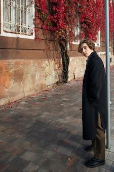Небинарный человек в ретро-одежде на улице с копией пространства