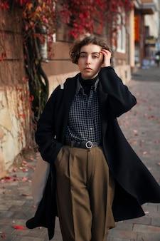 Небинарный человек в ретро-одежде снаружи