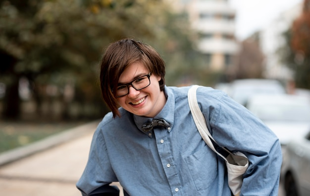 Non binary person with glasses smiling