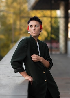 Non binary person with modern hairstyle looking away outside