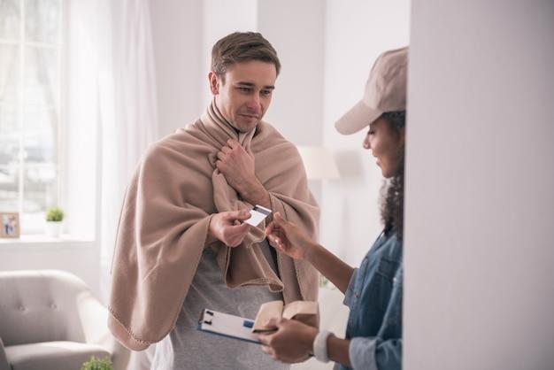 Безналичный расчет. больной молодой человек дает курьеру кредитную карту при оплате заказа