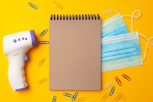 종이 클립과 노란색 배경에 비접촉 적외선 온도계. 코로나 바이러스 봉쇄 후 새로운 교육 지침 개념