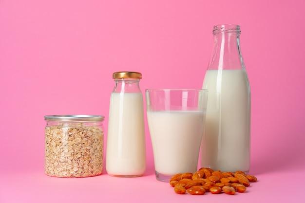 분홍색 배경에 유리 그릇에 견과류로 만든 비 유제품 비건 우유