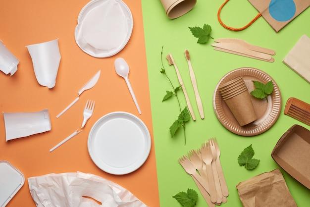 Неразлагаемые пластиковые отходы от одноразовой посуды и набор посуды из экологически чистых переработанных материалов на зеленом фоне