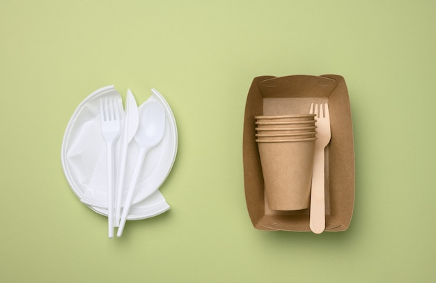 使い捨て食器からの非分解性プラスチック廃棄物と、緑の表面にある環境リサイクル材料からの食器一式。プラスチックの拒絶、環境保全の概念