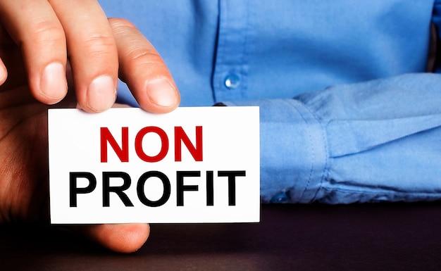 Non profitは、男の手の白い名刺に書かれています。広告のコンセプト