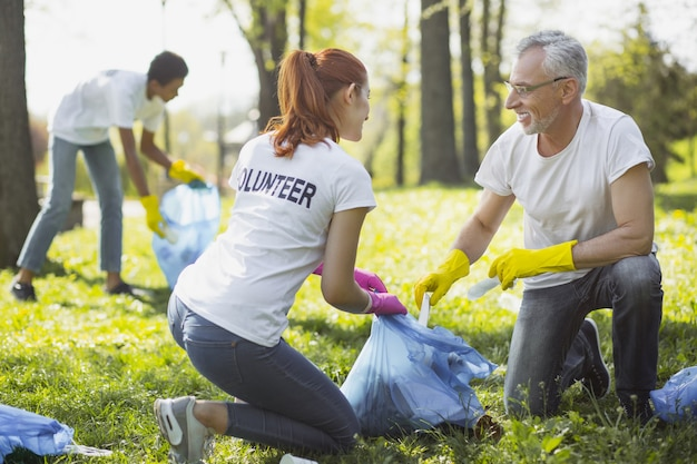 Некоммерческий волонтер. два энергичных волонтера держат мешок для мусора и болтают