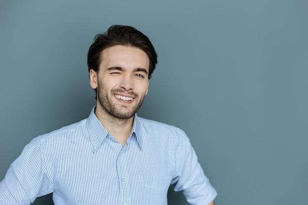 非言語言語。あなたを見ながら笑顔でウインクする陽気な前向きな幸せな男