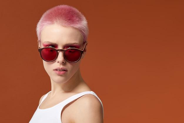 不適合な若い女性マゼンタの短い髪のピンクと赤いサングラス