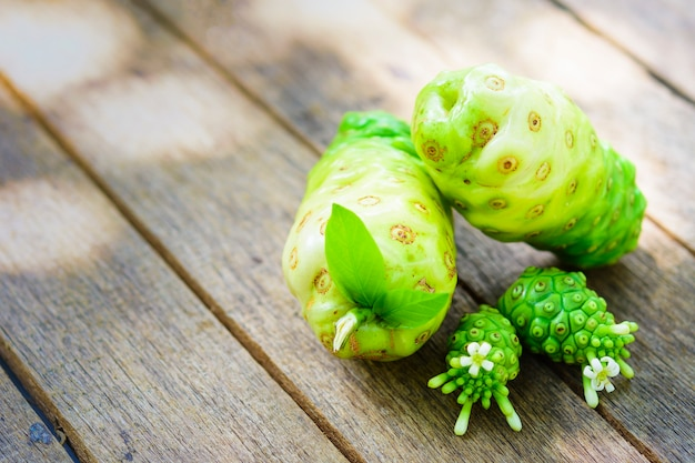 Noni fruit and blossom on old wooden table.