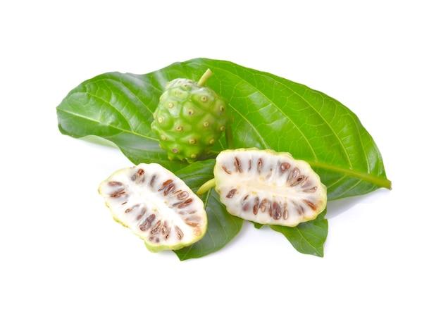 白い表面の大きな緑の葉のノニ果実