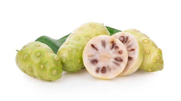 Плоды нони или morinda citrifolia с нарезанными и зелеными листьями, изолированные на белом фоне
