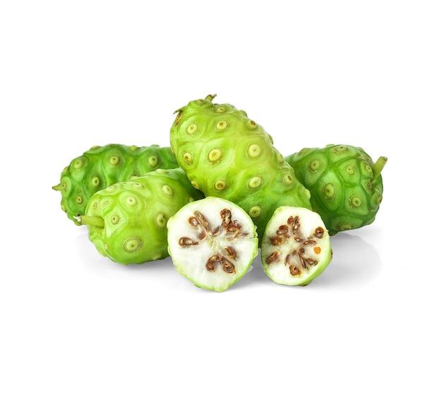 Плоды нони или morinda citrifolia с нарезанными и зелеными листьями, изолированными на белом