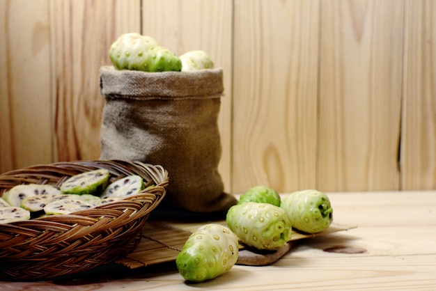 Noni in sack and noni slice in basket on wooden background..jpg
