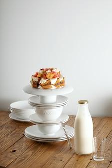 白いカップとソーサーのピラミッドの上にクリーム、チョコレート、グレープフルーツのバランスが取れた非伝統的なウエディングケーキとその隣に牛乳瓶