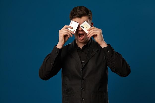 파란색 스튜디오 배경에 포즈를 취하는 동안 두 개의 카드 놀이를 들고 검은 조끼와 셔츠에 포커에 멍청이 ...