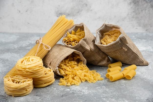 素朴なバスケットと大理石のテーブルの麺とパスタの品種。