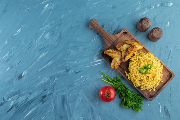 大理石の背景に、野菜の横にあるボード上の麺と翼。