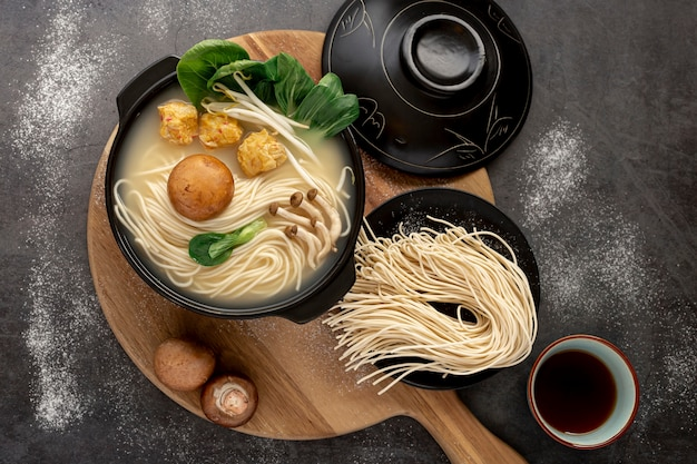 Noodle bowls on a wooden plate on a grey background