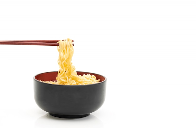 Noodle chopsticks in a black bowl on a white background