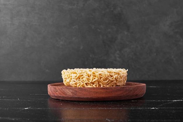 Кубик лапши в деревянной тарелке на черной поверхности