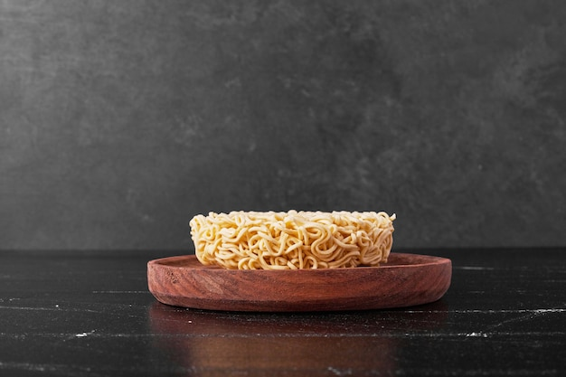 Noodle cube in a wooden plate on black surface