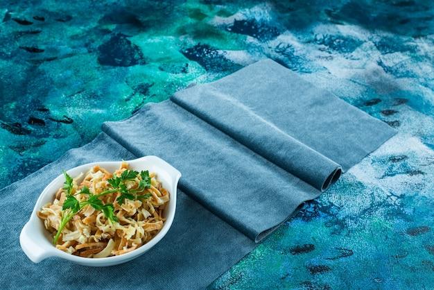 青いテーブルの上で、一枚の布の上にボウルに麺を入れます。