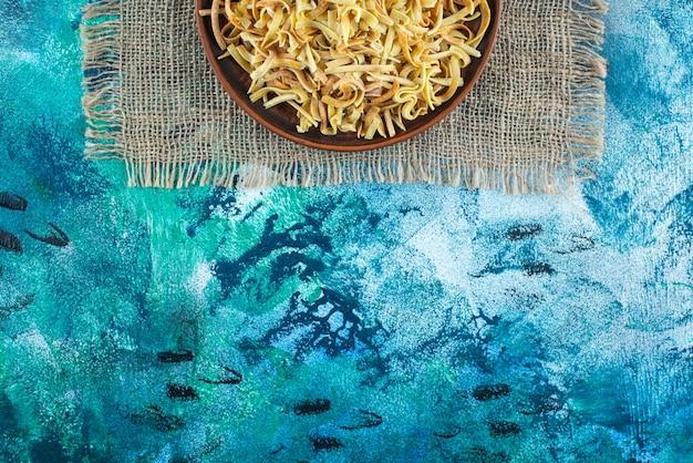 Лапша в миске на текстуре, на синем столе.