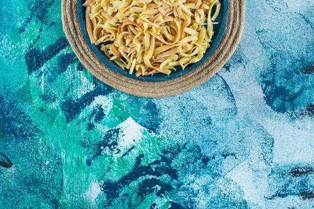 파란색 배경에 삼발이에 그릇에 국수.