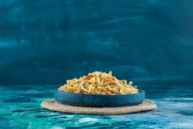 青いテーブルの上で、トリベットのボウルに麺を入れます。