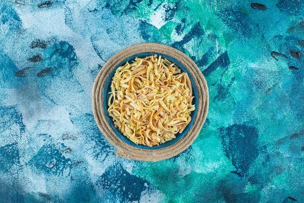 青のトリベットのボウルに麺。