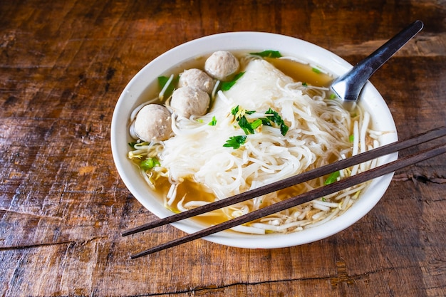 Noodle and meatballs in a bowl on a wooden table