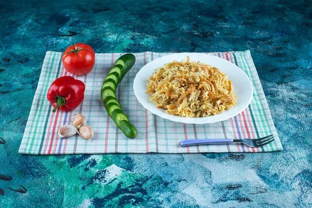 青いテーブルの上で、さまざまな野菜の横にある皿に麺を置き、ティータオルにフォークを置きます。