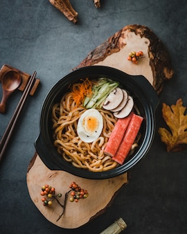 Noodle pasta with vegetables and egg on bowl, top view