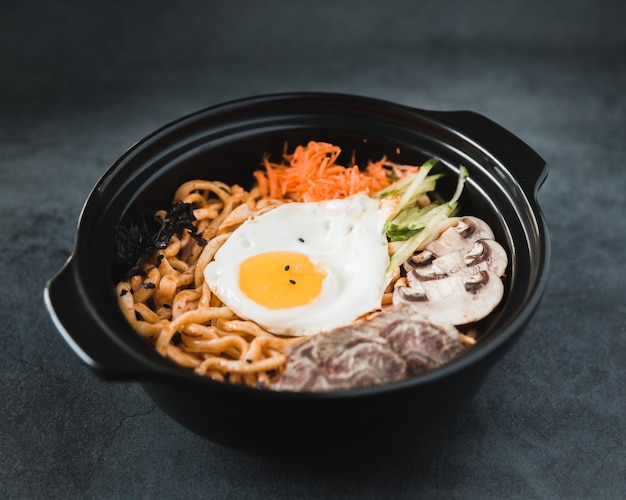 Noodle pasta with vegetables and egg on bowl