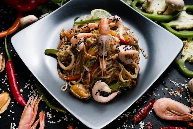 Лапша, креветки, креветки, морепродукты и овощи на тарелке