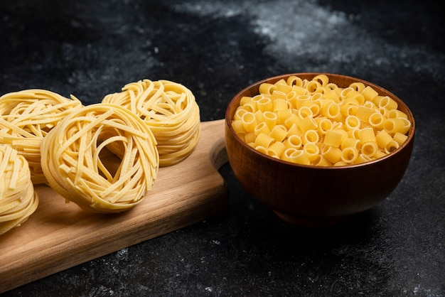 Noodle rolls on a wooden board with pasta varieties in wooden cups.