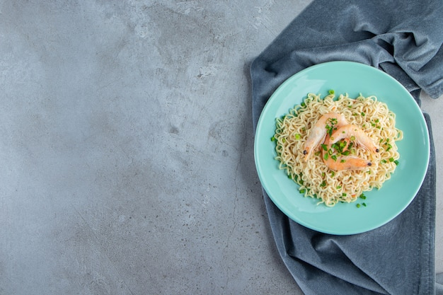 Noodle e gamberetti su un piatto su un pezzo di tessuto, sullo sfondo di marmo.