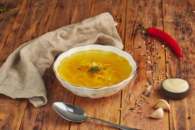 Суп с лапшой в миске, ложка на деревянном столе